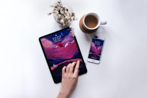 An ipad and iphone laying on a table with a cup of coffee and vase of flowers