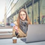 Woman sitting at laptop and looking at a credit card as if considering trustworthiness of the website