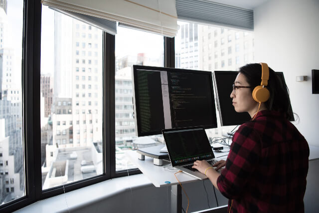 Woman working on computer with multiple monitors while looking out the window.